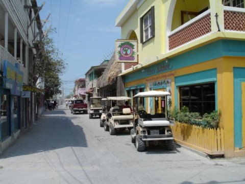 Narrow sand streets lined with golf carts on a bright, hot, sunny day in the town center of San Pedro, Ambergris Caye.