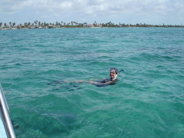 Snorkeler in clear, shallow waters over the reef, just offshore of Ambergris Caye, Belize.