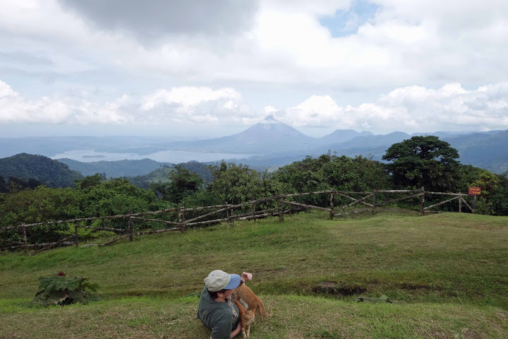 Lynn and kittens overlooking Arenal volcano and lake, Costa Rica.